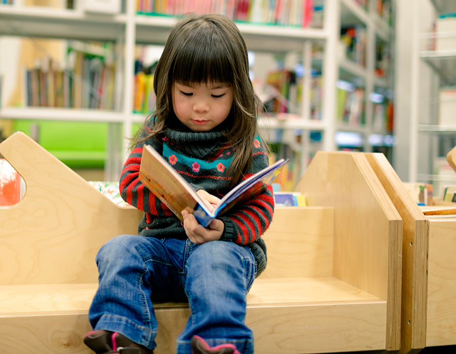 Small asian child reading children's book on a wood library bench