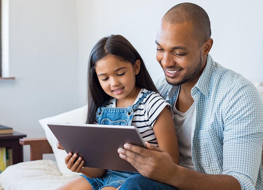African American man reading off of his iPad with his daughter