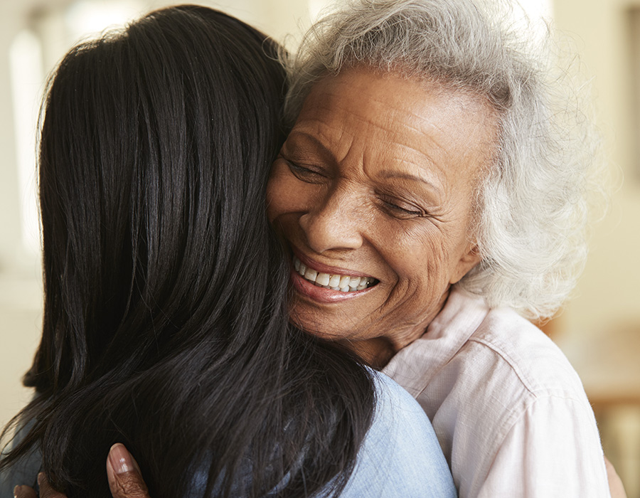 Older woman hugging another woman and smiling