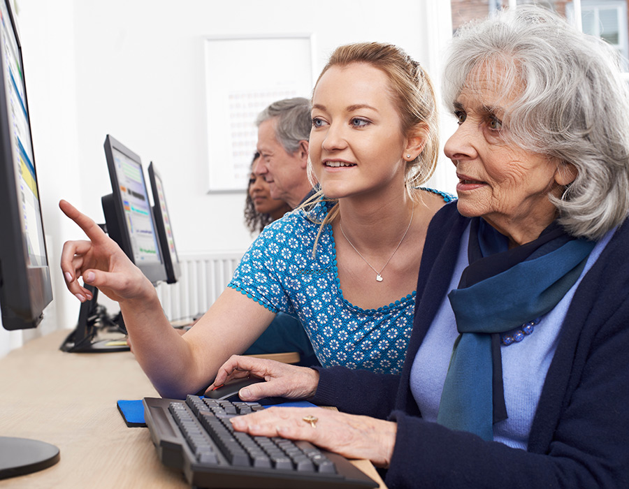 Woman helping an older lady learn how to use a computer