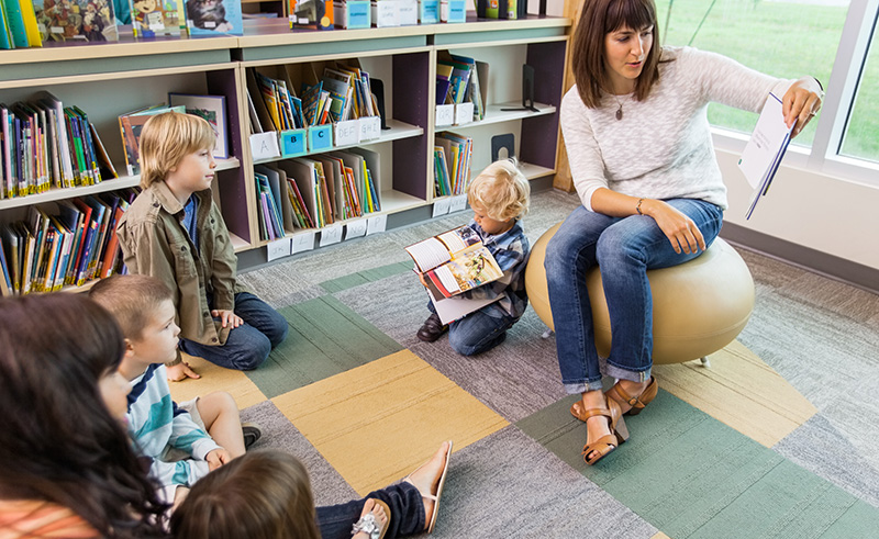 Women reading a children's book for storytime while a group of children listen
