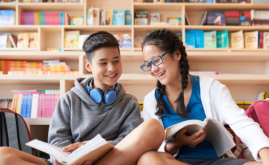Teens reading books next to eachother and smiling