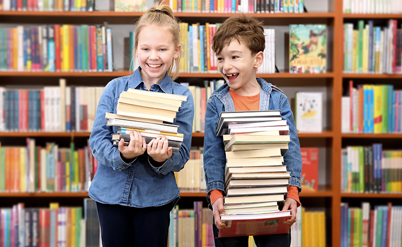 Children holding a stack of books and smiling