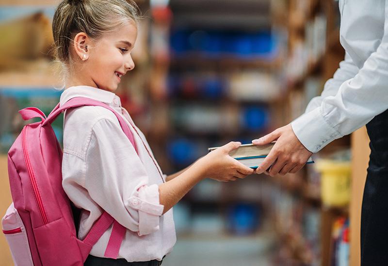 teacher giving books to schoolgirl.