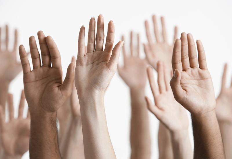 Closeup of multiethnic men and women raising hands against white background.