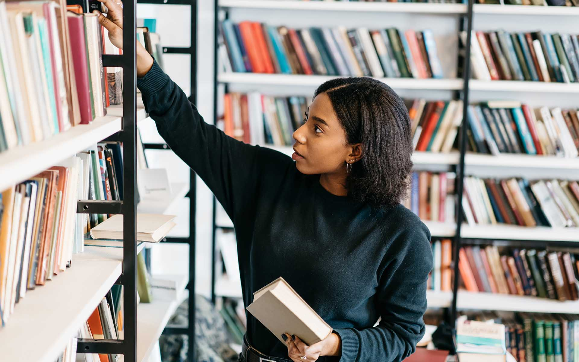 Young female african american librarian making order on bookshelf.